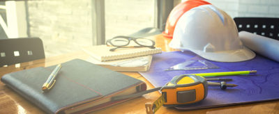 Hard hat and measuring tape at a desk